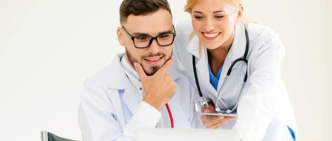male-female-doctors-working-laptop
