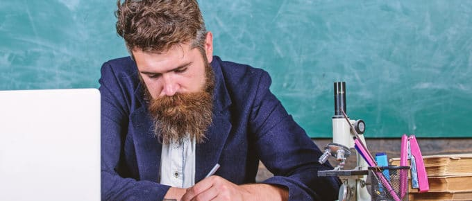 male-teacher-paperwork-desk-laptop