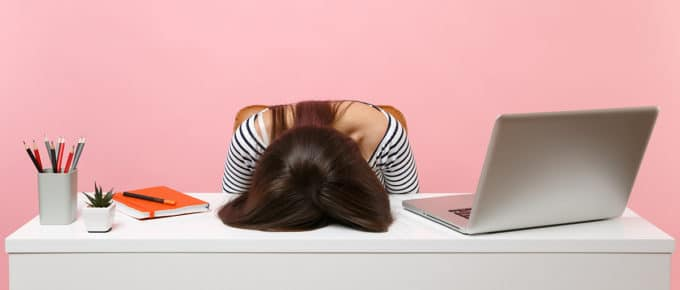 frustrated-young-woman-head-on-desk