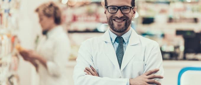 smiling-male-pharmacist-pharmacy-background
