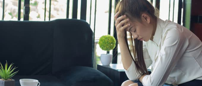 stressed-young-woman-sitting-holding-head