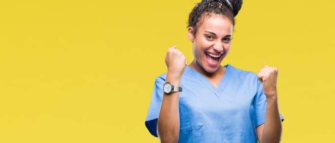 young-female-nurse-pumping-fists-yellow-background