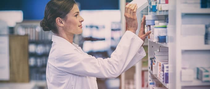 woman-pharmacist-putting-medicine-shelf