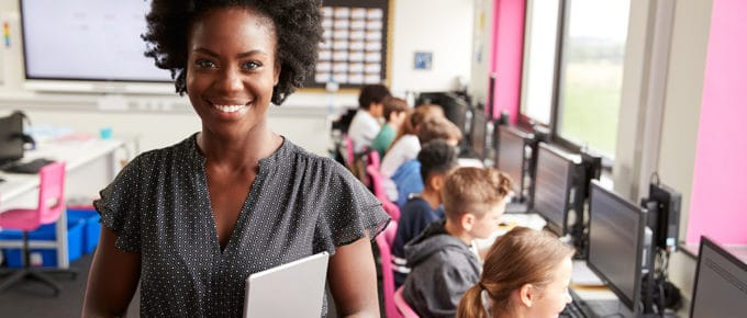 young-female-teacher-smiling-high-school-students-computers