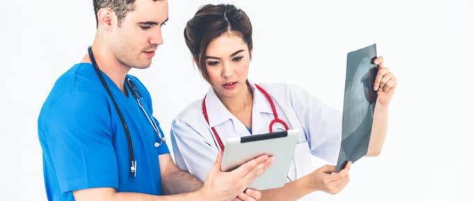 male-nurse-female-doctor-comparing-x-ray-notes