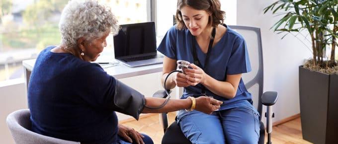 young-female-nurse-taking-blood-pressure-older-patient