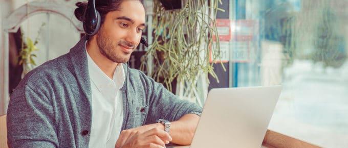 young-man-using-laptop-headphones