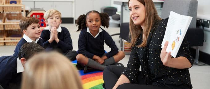 young-woman-teacher-reading-book-primary-students