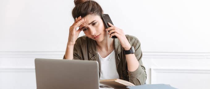 stressed-young-woman-calling-mobile-phone-laptop