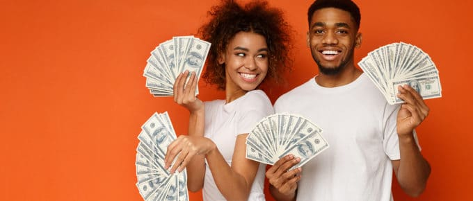 excited-young-couple-holding-money-fans