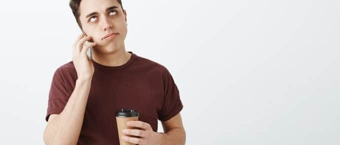 annoyed-young-man-mobile-phone-holding-coffee-cup-rolling-eyes