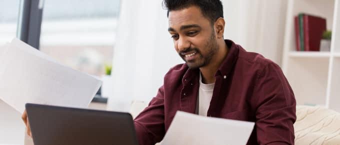 man-confused-financing-laptop-paper-bills