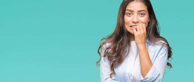 stressed-woman-biting-nails-teal-background