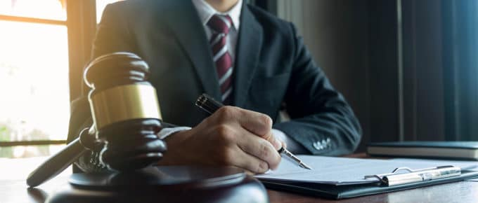 male-lawyer-writing-paperwork-desk-gavel