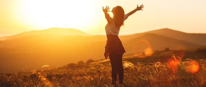 successful-woman-arms-raised-basking-sunset-open-field