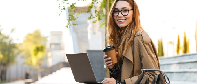 young-woman-holding-coffee-laptop-sitting-bench