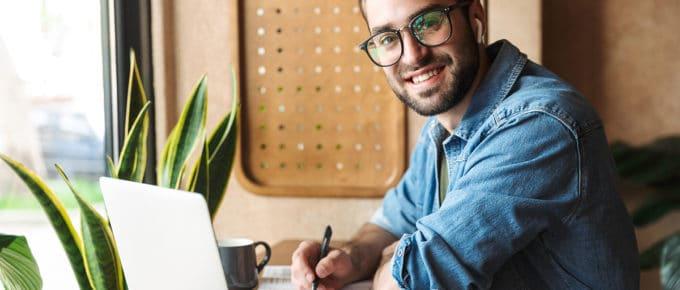 man-filling-out-paperwork-laptop