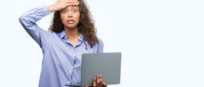 frustrated-young-woman-hand-forehead-holding-laptop-gray-background