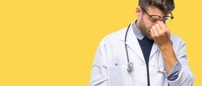 stressed-young-male-doctor-yellow-background