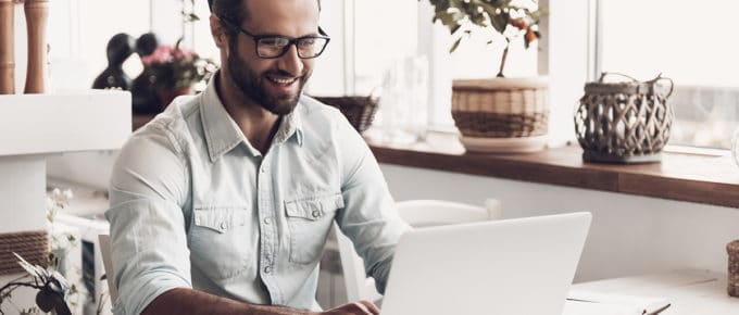 man-working-laptop-smiling-cafe