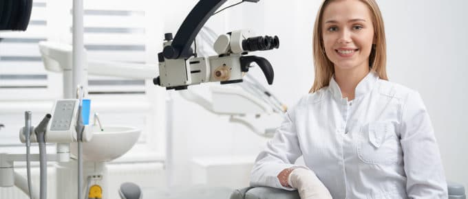 young-female-dentist-leaning-dental-equipment