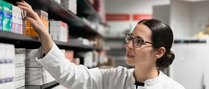 woman-pharmacist-reaching-for-medication-pharmacy-shelves