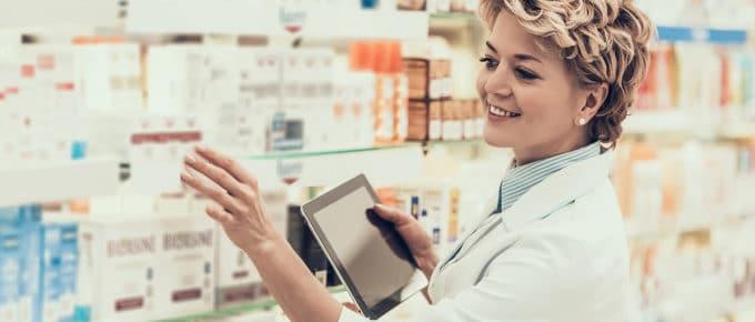 female-pharmacist-reaching-for-medicine-pharmacy-shelf